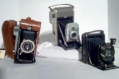 CA116-118 all accordion fold, Pocket cameras,  CA116- has form fit leather case w/wrist strap. CA 117- CA118 have hard cases w/wrist strap.