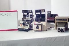 CA156 polaroid Sun 600 LMS w/strap, CA157 One step close upw/strap,  CA158 Impulse pop-up flash, Red,  CA159 One Step w/rainbow stripe, & strap,  CA160 Land camera swinger model 20,  w/wrist strap,  CA161 Kodamatic instant camera, pleaser 2 w/side handle