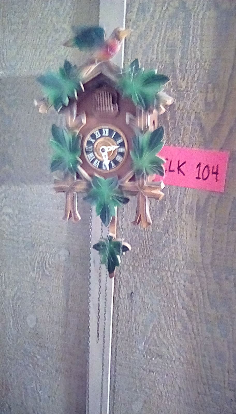 CLK104 wooden Black Forrest cuckoo clock w/green leaves, a bird on top,& 2 weighted pine cone pendulums